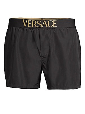 "Image of European cut swim shorts with sleek logo band Elasticized waist Back patch pocket Rise, about 10"" Leg opening, about 21"" Inseam, about 3"" Polyester Machine wash Made in Italy. Men Modrn Dsgn - Versace. Versace Collection. Color: Black. Size: 7 (XL)."