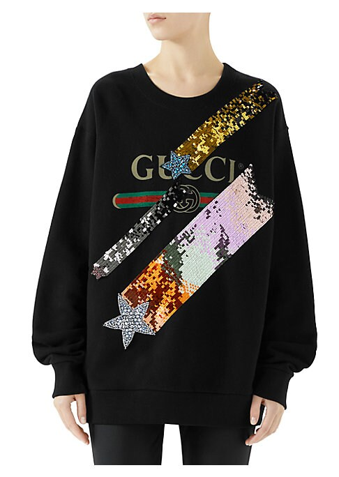 "Image of Gucci logo sweatshirt with jeweled shooting stars. Crewneck. Long sleeves. Pullover style. Crystal shooting star applique. Embroidered sequins. Gucci vintage logo. Oversize fit. About 24"" from shoulder to hem. Cotton. Machine wash. Made in Italy. Model sh"