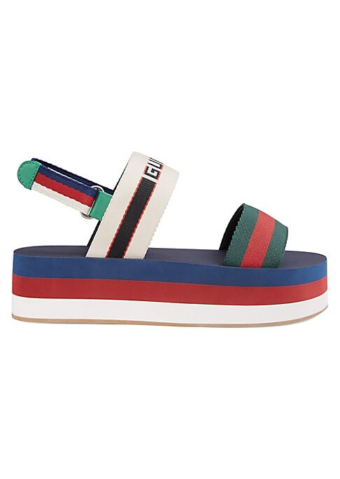 Image of Gucci stripe platform sandal. Orange nylon Gucci stripe elastic. Sylvie Web stripe platform. Velcro ankle strap. Rubber sole. Made in Italy.