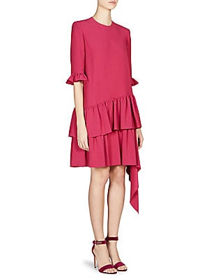 Image of Adorned with tiered and cascading ruffles, this structured shift dress is a playful statement piece. Roundneck Short ruffle cuff sleeves Concealed back zip closure Tiered asymmetric ruffle hem Viscose/acetate Dry clean Made in Italy SIZE & FIT Shift silho