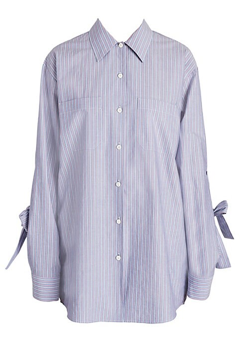 Image of Miuccia Prada revisits the classic button-down from menswear; her oversize version stars a delicate two-tone stripe which runs the length of the shirt. Exaggerated bow ties on the sleeve act as a feminine touch, and a feminist comment, from the intellectu