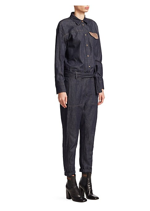 Image of Jumpsuits are having a moment, and this denim iteration flaunts a chic belted finish. The single embellished pocket adds a glimmer of femininity to the menswear-inspired silhouette. Spread collar. Long sleeves. Button front close. Belted waist. Chest flap