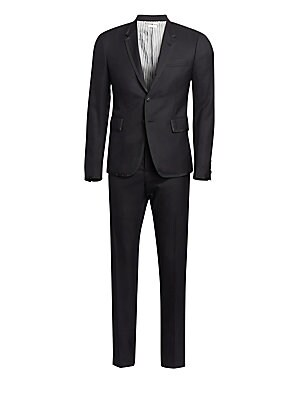 Image of Twill wool tuxedo framed by grosgrain trim and featuring a high armhole jacket and low-rise skinny trousers. Super 120s wool. Dry clean. Made in Italy. JACKET Notch lapels with buttonhole Long sleeves High armholes Buttoned cuffs Two- button single breast