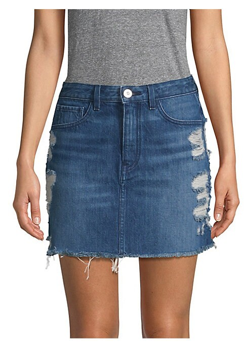 """Image of From the Saks It List: The Mini Skirt. Frayed hem jean skirt in faded distressed style. Belt loops. Five-pocket style. Button and zip fly. About 15.75"""" long. Cotton. Machine wash. Made in USA. Model shown is 5'10"""" (177cm) wearing US size 4."""