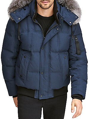 Image of Warm down filled quilted bomber trimmed with a luxe fox fur hood. Removable drawstring fur-trimmed hood Stand collar Long sleeves Front zip with covered snap button placket Side button flap pockets Arm zip pocket Rib knit hem and cuffs Lined Polyester/ela