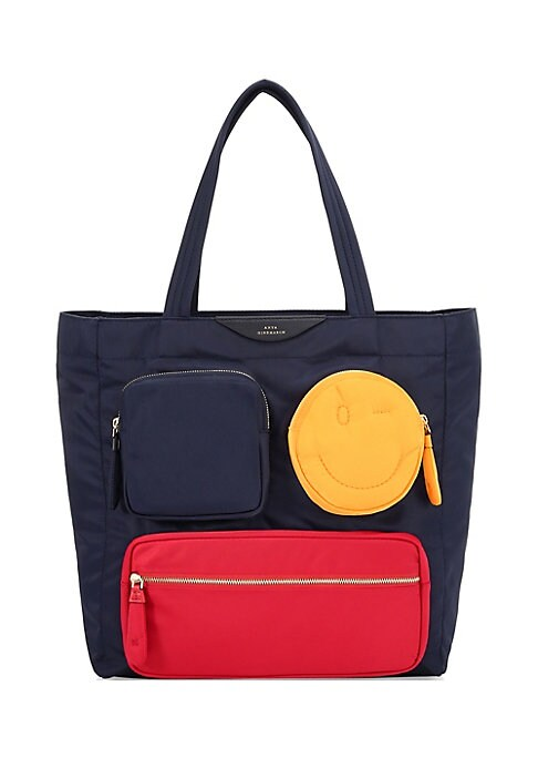 Image of Anya Hindmarch's quirky design is evident in this expressive tote with pockets that resemble a wink. Top zip closure. Goldtone hardware. Three exterior front zip pockets. One interior zip pocket. Fully lined. Nylon. Imported. SIZE & FIT. Double top handle