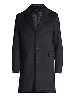 Image of This stretch wool waterproof coat features an attached quilted bib. Notch lapels Long sleeves Quilted zip-up bib lining Front button closure Slip pocket at chest Flap pockets at waist Structured seams Vented hem Polyester/wool Dry clean Imported SIZE & FI