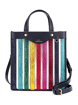 """Image of From the Saks It List: Bold Stripes Chic transparent tote with shimmering rainbow stripes Double top handles Interior slip pocket 13.5""""W x 14.25""""H x 6""""D Leather/synthetic Imported. Handbags - Advanced Designer Handba. Anya Hindmarch."""