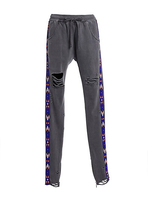 Image of Drop-crotch tapered joggers with Navajo-inspired beaded side stripes. Allover distressing and ankle zips add a rock-and-roll edge to these cotton pants. Elasticized drawstring waist. Pull-on style. Side slash pockets. Ankle zips. Cotton. Dry clean. Made i