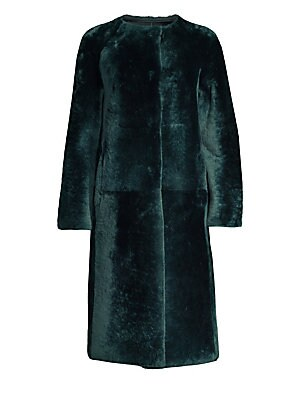 Image of This bold shearling coat exudes glamour and allurement. Plush to the touch and crafted in a boxy silhouette, this is a piece that redefines refinement. Roundneck Long sleeves Concealed button front Side seam waist pockets Fuzzy finish Shearling Fur type: