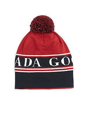 """Image of Iconic logo toque flaunts a fuzzy pom pom. Merino wool Dry clean Made in Italy SIZE Length, 7"""". Soft Accessorie - Cold Weather Accessories. Canada Goose. Color: Redwood."""