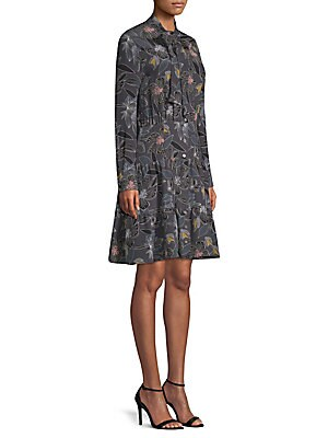 "Image of Flirty shirt dress features a tiered flounce skirt and tie neck accent. Self-tie neck Long sleeves Button cuffs Button front Gathered detail Lined Silk Dry clean Made in USA SIZE & FIT A-line silhouette About 38"" from shoulder to hem Model shown is 5'10 ("