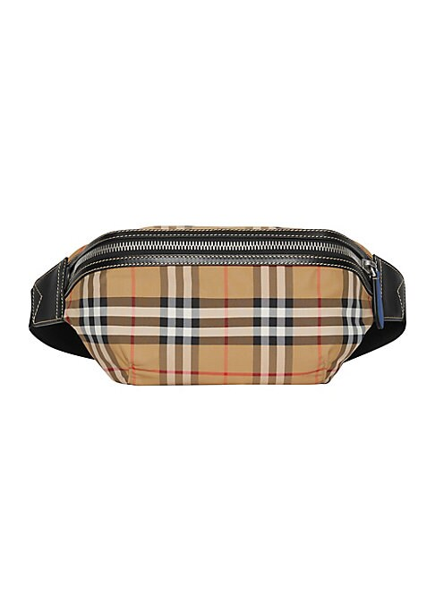 Image of A 1990s streetwear staple revived in vintage-inspired check with leather accents. Carry it crossbody, by the strap or around the waist. Zip-around closure. Silvertone hardware. Lined. Polyamide. Trim: Leather. Made in Italy. SIZE. Adjustable buckle belt,