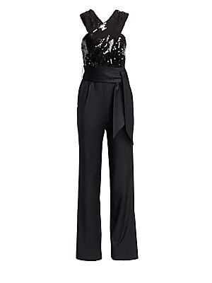 Image of From the Saks It List: The Jumpsuit Stunning sleeveless jumpsuit with crossover sequin top and flattering v-back. Made in France, this statement piece also features a wide sash belt and straight-leg silhouette. Crossover neck Sleeveless V-back Belt loops