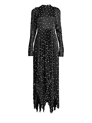 Image of From the Saks It List: The Maxi Dress There's an art to party dresses, and Khaite's Catherine Holstein has nailed it here. Flocked velvet polka dots stand out against a black backdrop, with soft puff sleeves matched with a pleated, handkerchief hem skirt.