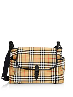 Image of A baby-changing shoulder bag in resilient canvas check with rich leather trims. Complete with multiple pockets and a fold-out changing mat. Adjustable shoulder strap Top flap with magnetic closure Two exterior side slip pockets Back exterior slip pocket w