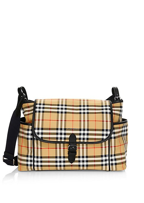 Image of A baby-changing shoulder bag in resilient canvas check with rich leather trims. Complete with multiple pockets and a fold-out changing mat. Adjustable shoulder strap. Top flap with magnetic closure. Two exterior side slip pockets. Back exterior slip pocke