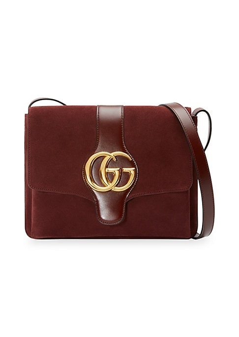 "Image of Double G.Adjustable shoulder strap, 15"" drop. Magnetic snap flap closure. Goldtone hardware. One interior zip pocket. Two interior sections.10.5""W x 8""H x 1.5""D.Lined. Suede. Leather trim. Made in Italy."