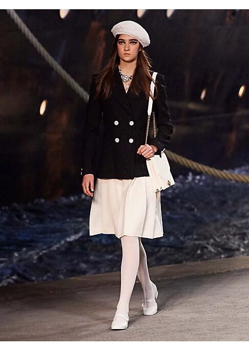 Image of SKIRT. Wool Crepe, White.$2,650.Style Code: 0400099812293.MARY JANES. Calfskin, White.$875.Style Code: 0400099651955.JACKET. Wool Crepe, Black.$5,350.