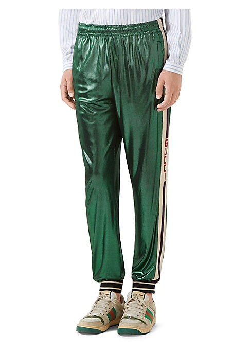 """Image of Elastic waistband with internal drawstring. Front pockets. Gucci jacquard stripe along the legs. Striped trim. Laminated jersey. Loose fit. Rise, about 11"""".Inseam, about 38"""".Leg opening, about 12"""".Acetate/polyamide. Dry clean. Made in Italy."""