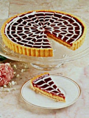 """Image of A butter cookie tart shell is filled with a crunchy, chewy almond filling, topped with seedless raspberry jam, and finished with a decorative swirled glaze.""""Outstanding Dessert"""" winner, International Fancy Food Show. Hand made and decorated.9?"""" diameter.N"""