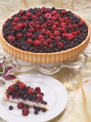 """Image of Berry, berry yummy! A butter cookie tart shell is filled with a light, almond flavored pastry cream and topped with a mountain of wild blueberries and raspberries.""""Outstanding Dessert"""" winner, International Fancy Food Show. Hand made and decorated.9?"""" dia"""